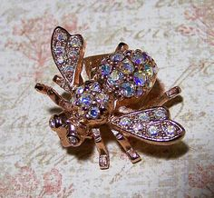 Joan Rivers rose gold flying bee brooch Bug is encrusted in aurora borealis crystal rhinestones Signed Joan Rivers 1 x 1 3/8 inches Good vintage condition, shows no wear I specialize in vintage figural animaljewelry, please visit my shop for more selections International buyers