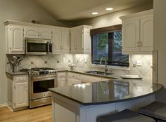 The Cambria Quartz countertops and the tailed tile backsplash are highlighted by under-cabinet lighting and blend beautifully with the color scheme. Visit our portfolio for Before & After pics of this and other remodels by Design Connection, Inc. Kansas City Interior Designer http://designconnectioninc.com/portfolio