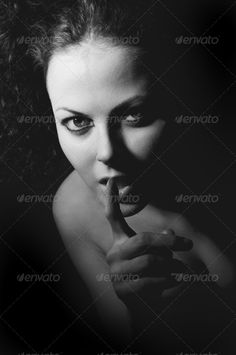 Girl Shows Silence Gesturing ...  adult, background, beauty, black, caucasian, close-up, concepts, confidence, danger, dark, expression, face, facial, female, finger, forbidden, gesturing, gossip, hand, head, human, indoors, lips, monochrome, mouth, mystery, one, person, portrait, privacy, secrecy, secret, sensuality, shadow, sign, silence, studio, surprise, symbol, warning, whispering, woman, young