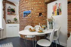 ściana z czerwonej cegły w białej kuchni,biały owalny stół na metalowych…