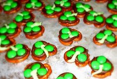 First we covered a cookie sheet with waxed paper. Then we covered the cookie sheet with a single layer of pretzels and put a Hershey's kiss on each and every pretzel. Then we put them in the oven at 200 degrees until they were all warm and melty and oh so delish.    Then we took them out of the oven and put 3 green M&M;'s on each kiss. We put them in the fridge until the chocolate set back up. Then we added a line of green frosting to make the stem. The frosting was greener in real life, it l...