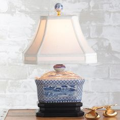 Mini Canister Table Lamp Blue and white oriental scene is hand painted on a ceramic canister and set on a double black base for a mini yet mighty porcelain possession!
