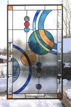 Galaxy grand Vertical - 17 x 29 1/4 - Stained Glass Window Panel Présenté ici est une autre version de la conception de panneau Galaxy mais, avec un fond de verre clair texturé et un peu d'un jeu de couleurs différentes. C'est un design intéressant des cercles et des arcs suggérant interaction planétaire. Le panneau interne est bordé par les biseaux, verre clair texturé et verre rayé orange dans les coins. Il a un visuellement large, 3/8 de profondeur zinc cadre 1/4 autour de ...