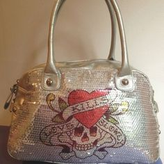 """""""Love Kills Slowly"""" SEQUINED Double Handled HOBO 100% AUTH Signature Ed Hardy Hobo style. Front totally sequined w/skull & words"""" Love Kills Slowly""""  Back solid silver w/ """"ed hardy"""" in red. Gusseted sides w/3 hallmarked rivets & square ring detailing. Top Zip is very substantial w/hallmarked rivet on pull. DBL handles w/rivets Interior black """"silk"""" w/repeat silver logo detailing. 1 Divided 2-compartment open pocket on 1 side, safety compartment w/silver zipper pull & hallmarked rivet on…"""