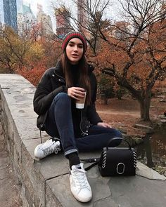 A cozy beanie with a puffer jacket, cuffed jeans, and sneakers.