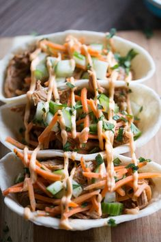 Bbq pulled pork with an asian flair! These taco boats start with pork that is slow cooked in an Asian inspired sauce then topped with cucumbers, carrots and Sriracha mayo! lemonsforlulu.com
