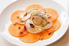 Persimmon Carpaccio with Fennel Salad (via Organic Authority)  Vegetarian, vegan and gluten free   Serves 4  10 minutes        * 2-3 fuyu persimmons      * 1 bulb fennel (reserve fronds)      * 4 radishes      * 1/4 of a small red onion, peeled      * 2 tablespoons extra-virgin olive oil      * 1 tablespoon champagne vinegar      * 1/2 teaspoon flaky sea salt (preferably Maldon)      * 2 tablespoons toasted pumpkin seeds (pepitas)