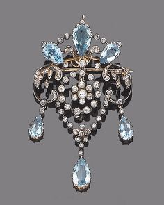 A belle epoque aquamarine and diamond brooch/pendant, circa 1910. The openwork cartouche set with rose-cut diamonds and pear-shaped aquamarines, suspending a cicular millegrain-set old brilliant-cut diamond swag centre and terminating in three collet-set rose-cut diamond and pear-shaped aquamarine drops, mounted in silver and gold, diamonds approx. 0.70ct. total, length 6.0cm.