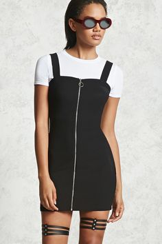 A combo dress featuring a cropped knit tee with a crew neck, short sleeves, an attached ribbed stretch knit cami dress overlay, a high-polish zip front with an O-ring pull, and a bodycon silhouette.