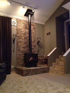 We like this stone hearth/dais thing for the gas stove. We like that it's up off the floor, we like the stone wall, we like the flanking sconces  Lisa: I love natural looking stone but not this stone in particular