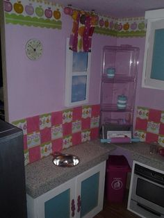 The windows in kitchen/living room are made from a trifold picture frame that I painted and added some scrapbook paper to. We can take the windows down and change the scenes as she likes. The plastic shelf is a basic plastic tray and the metal recipe holder is a business card older. The stove was printed out and glued to the front of one of the cabinet doors. I still need to finish the sink and stovetop eyes. The trash can was from the Dollar Tree and the curtains are scraps of from other rooms.