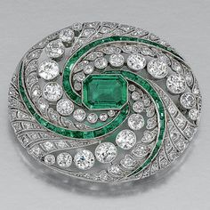 EMERALD AND DIAMOND BROOCH, CIRCA 1910.  The oval brooch centring on a rectangular cut-cornered emerald within an open work foliate surround of millegrain circular- and single-cut diamonds and calibré-cut emeralds.