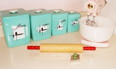 1950s turquoise canister with a stand mixer, red-handled rolling pin, and cookie cutter.