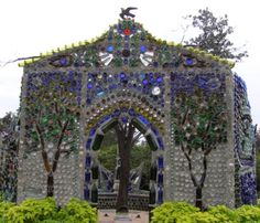 "The entrance to a bottle house created by Virginia Wright-Frierson in 2004. It is officially named the ""Minnie Evans Sculpture Garden Bottle House"" after an artist/gatekeeper that worked there for many years. This bottle house is also referred to as the ""chapel"". Frierson used bottles, cement and chicken wire."