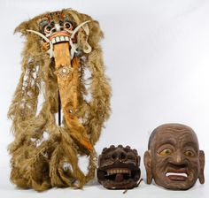 """Lot 191: Asian Decorative Masks; Three painted wood items including a mask of a male, a dragon mask and a mask with grass hair and fabric tongue; together with a 25"""" tall display mount"""