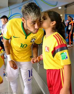 Good luck: Neymar receives a peck on the cheek from his player mascot before the Colombia game