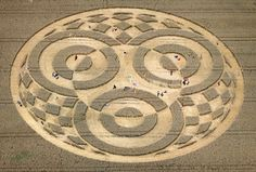 In this Monday, July 28, 2014 photo visitors walk through a crop circle in a wheat field near Raisting, southern Germany. A balloonist had discovered the crop circle about a week ago. Since then thousands of esoteric fans came to visit the circle whose appearance is unknown. Farmer Christoph Huttner, the owner of the field, says that he is not responsible for the crop circle. (AP Photo/dpa, Karl-Josef Hildenbrand)