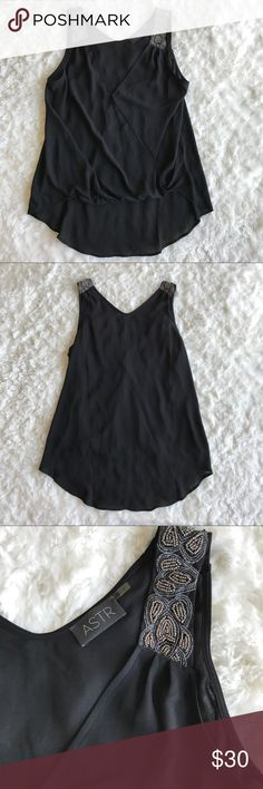"""NWOT ASTR Beaded Wrap Hi-Lo Tank Black sheer flowy tank. Beaded on the sleeves. Lower in the back and elastic on the bottom of front hem for surplice look. Button to hold wrap. 100% polyester. Dry clean. 24"""" in length in front and 26"""" in back. 19.5"""" in bust. ASTR Tops Tank Tops"""