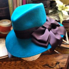 Dark turquoise blue fedora with big black bow from the Saucy Milliner