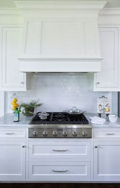 via Hendel Homes - a white kitchen with a classic white subway tile backsplash and a sleek Thermador range cooktop. Please check out the blog for more innovations from the Kitchen and Bath Industry Show in Orlando 2017.