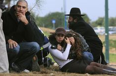 Israelis take cover during a rocket warning siren in the southern Israeli town of Ashkelon, Monday Dec. 29, 2008