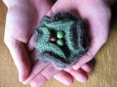 Two tone green crocheted brooch with wooden beads in the center. $13.00