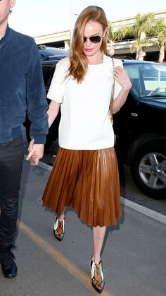 Kate Bosworth - street style.  The actress strategically offset the girly nature of a knife-pleated skirt with a casual white top and cool snakeskin boots.