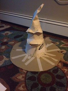 Use card board to make a large circle with the brim in the middle . Use oak tag or cereal boxes to make a cone shape for the top of the hat. Cut pieces for the eyebrows and mouth and tape together.