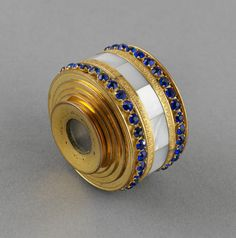 Gold, mother of pearl, sapphires, glass. A small telescope with five extending tubes springing from a base of gold with sapphire borders and a faceted mother of pearl centre band.