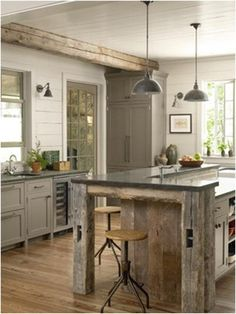 Love the color of the cabinets and reclaimed wood island and beam