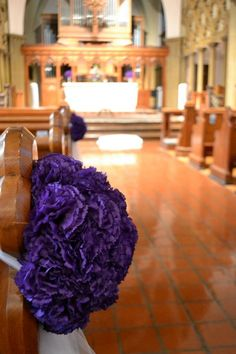 pew bows made with 6-inch styrofoam balls (halved) with a white tulle tie in the back and a yard of white tulle hanging down. Each half ball is filled with 35-40 high quality purple silk carnations.