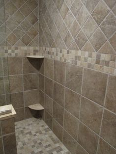 Often one corner of a shower is the key starting point. You can see how the designer of this tile layout started with half tiles in the corner, then worked out from there. At the entry to the shower, the eye is drawn to this corner with the bench, making the corner itself the shower's feature wall.
