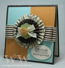 Medallion with print and solid paper fan folded rosettes, topped with die cut flower, lace bow, and tied together with jute cord laced through button. Very nice!