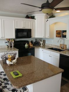 Darker granite on the island with white cabinets make the kitchen interesting and light. Love my kitchen for a small kitchen (townhouse). Did this 4 years ago because granite remnants are FREE!! and all you have to do is pay to have them cut and installed. The granite on the main counter is beautiful, but they didn't have a piece quite big enough, so I did the darker island, which matches the granite in the half bathroom.