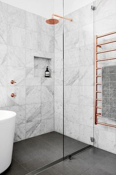 I love the copper taps, shower head and radiator against the marble tiles and state grey tiled floor in this modern bathroom.