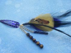 This feathered hair clip features a cool mix of purple, gold and black. The feather is accented by tiger's eye beads, black crystals and purple spacers.