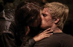 The Hunger Games: While caring for Peeta (Josh Hutcherson), Katniss (Jennifer Lawrence) leans in to give him a kiss.