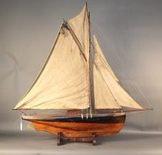 "Early 20th century ""Straight Line Racer"" pond yacht.  A straight line racer is an English racing class for model yacht racing.  The model is rigged with a full suit of sails, brass hardware, set onto a wood cradle.  49"" long x 10"" wide x 49"" tall Estimate: 2500 - 3500"