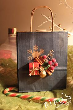 Blue handmade paper bag for Christmas presents with golden snowflake, cinnamon and decorations