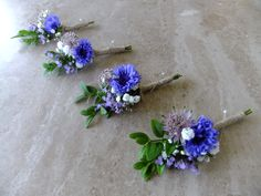 A set of four stylish Gentleman's buttonholes with blue cornflowers, pink astrantia and hebe finished with twine
