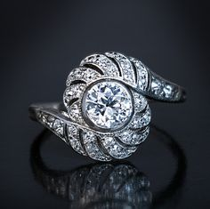 An elegant Art Deco platinum tourbillon ring, circa 1920s, centered with a bezel-set sparkling old European cut diamond surrounded by old single cut diamonds.