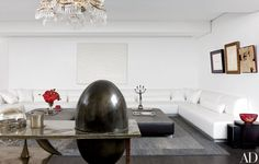 The living room features a metal bar made by François-Xavier Lalanne for Yves Saint Laurent and Pierre Bergé. A white nail-studded Enrico Castellani painting hangs above the Rovatti-designed sofa, as do works by (from left) Lucio Fontana, Henri Matisse, and Alberto Burri.