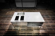 Alpes Inox Kitchen island unit made of stainless steel, with sink, hob and storage.
