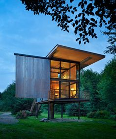 Sol Duc Cabin - Providing secure shelter for every season, this steel-clad 350 sf fishing cabin on stilts can be completely shuttered when the owner is away. The cabin's rugged patina and raw materiality respond to the surrounding wilderness while its verticality provides a safe haven during occasional floods from the nearby river.    Composed of two levels, the cabin's entry, dining and kitchen areas are located on the lower floor while a sleeping loft hovers above. A cantilevered steel dec...