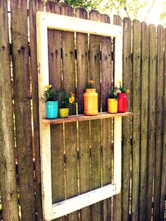 Easy decoration for your fence: old window, scrap piece of wood for shelf, jars you find around the house painted on the inside, add some plants and there you go!