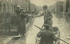 Norwich floods 1912. For those who remained in their homes, food and other supplies were delivered by boat or horse and cart. This is Lothian Street with Cushions woodyard seen on the right.