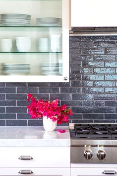 Tile backsplash in kitchen with glass shelves and vase of vibrant flowers