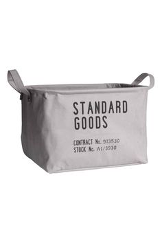 Storage basket: Storage basket in sturdy fabric with a text print motif, two handles, a concealed metal edge at the top for stability, and a plastic-coated lining. Size 23x29x36 cm.
