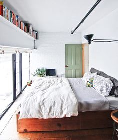 The bedroom is small but the white palette, lack of clutter and simple roll-up blinds keep the look simple. A black work lamp is angled upward for softer lighting above the bed. PHOTOGRAPHER: IDA MAGNTORN / LIVING INSIDE