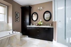 Love the tan walls with dark accent wood and circle mirrors!